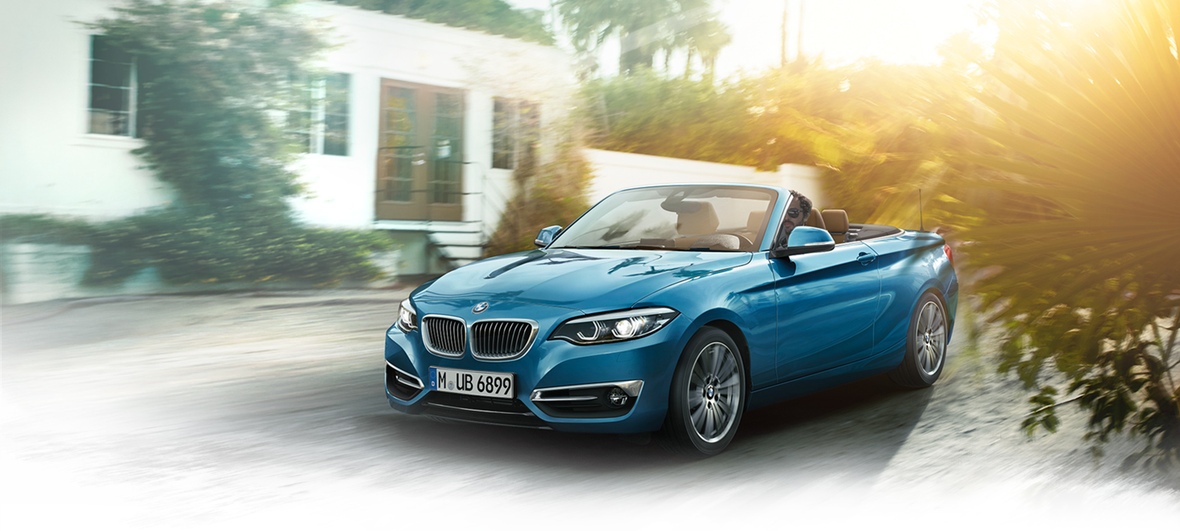 BMW 2-Series Convertible blue: frontside view by the houses