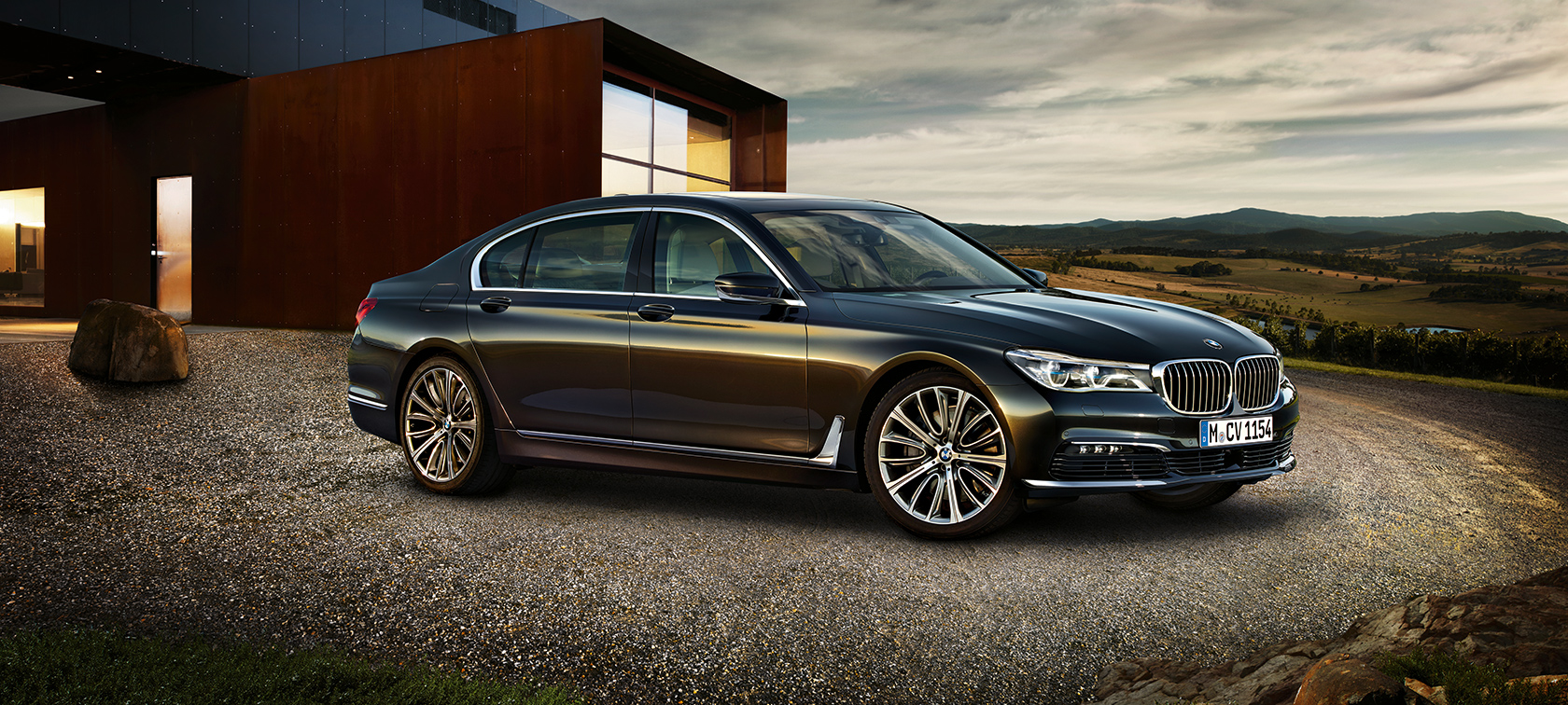 BMW 7-Series Sedan in black: frontside view close to luxury condo
