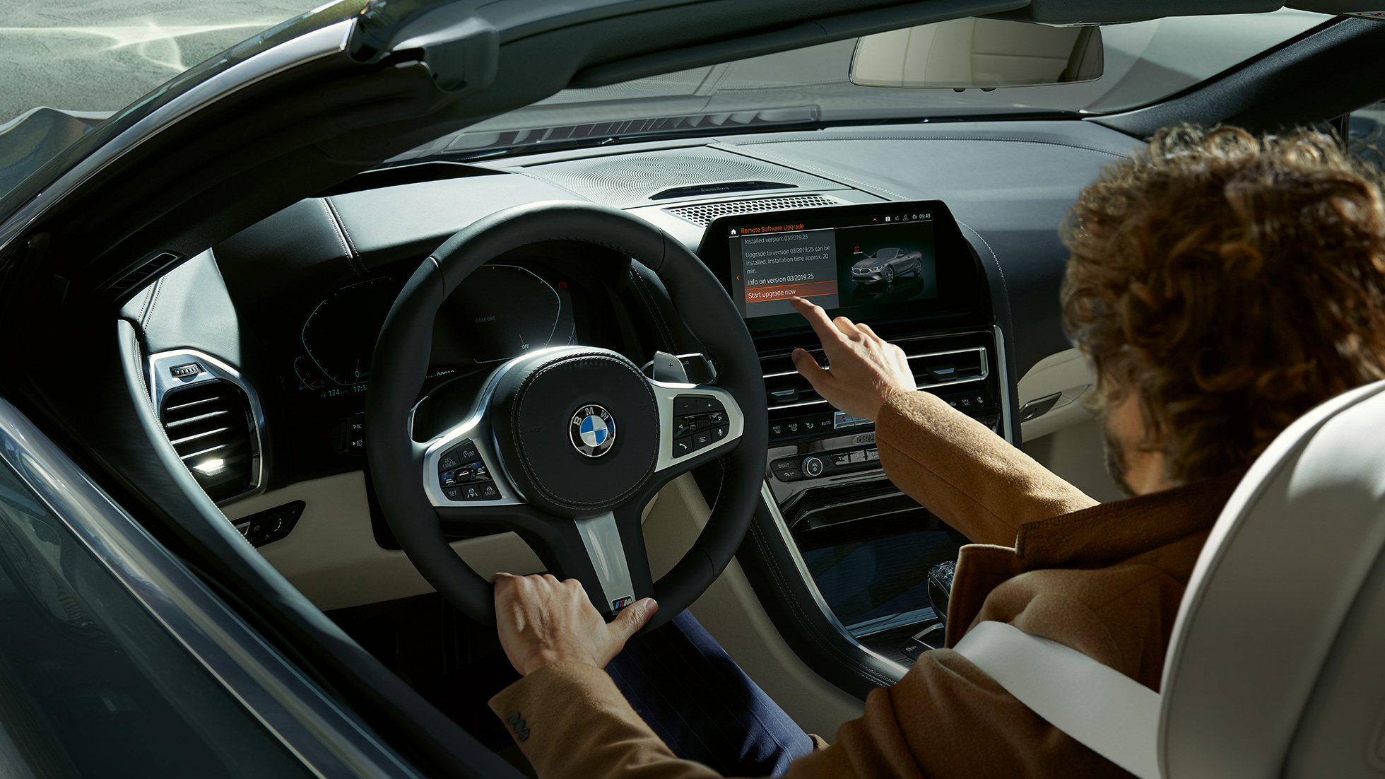 BMW M850i xDrive, driver operating BMW Live Cockpit Professional by touch control.
