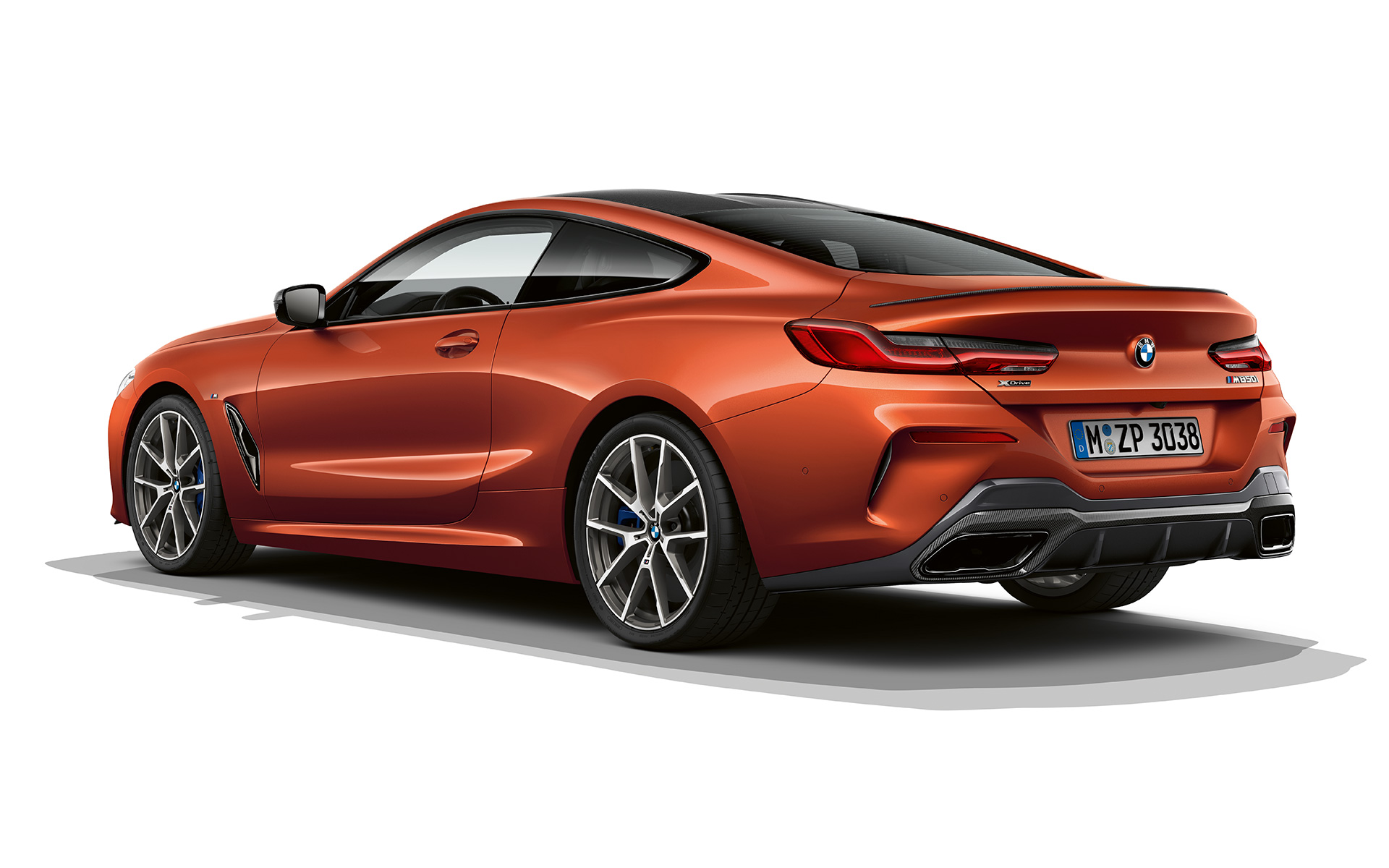 A still shot of the BMW 8 Series Coupé in Sunset Orange metallic against a white background.