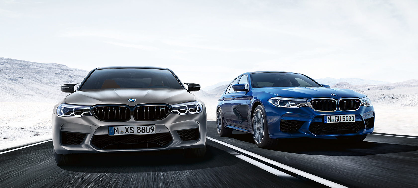 BMW M-Series M5 Sedan in silver and bright blue racing in snow