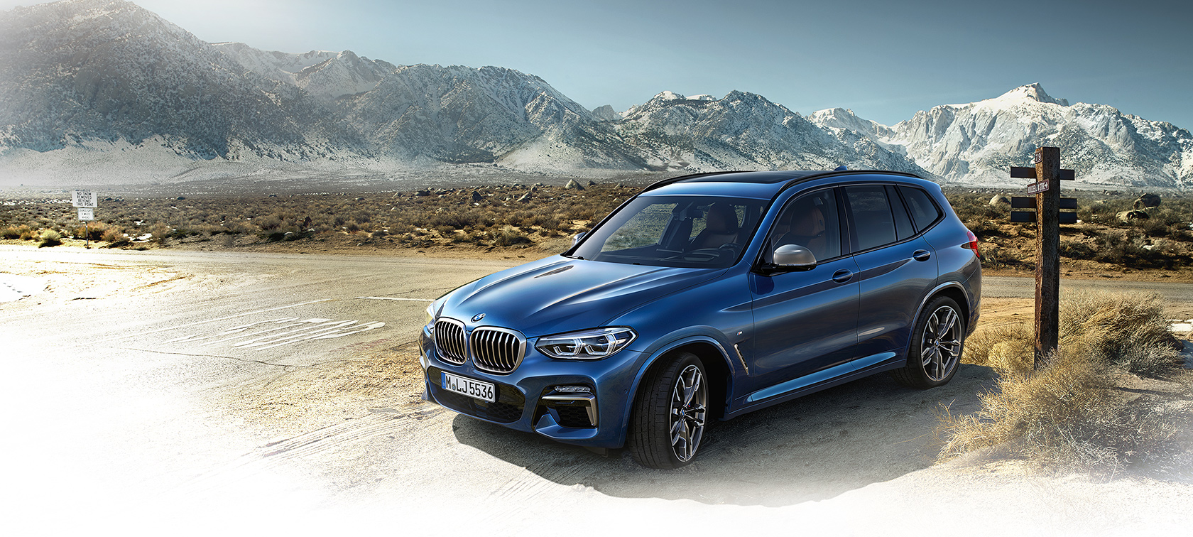 BMW X-Series X3 in bright blue frontside view: mountain road