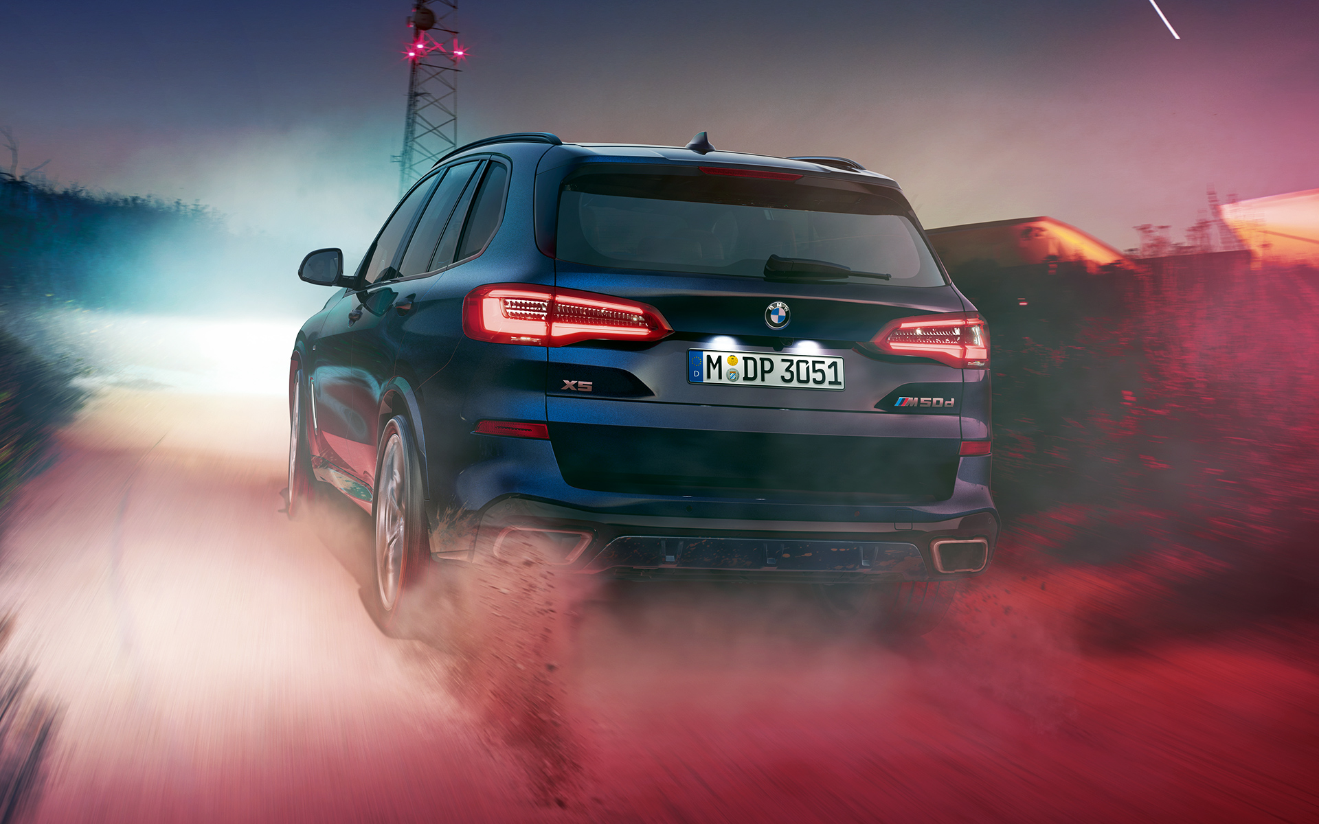 Rear of the BMW X5 M50d at night in an urban setting