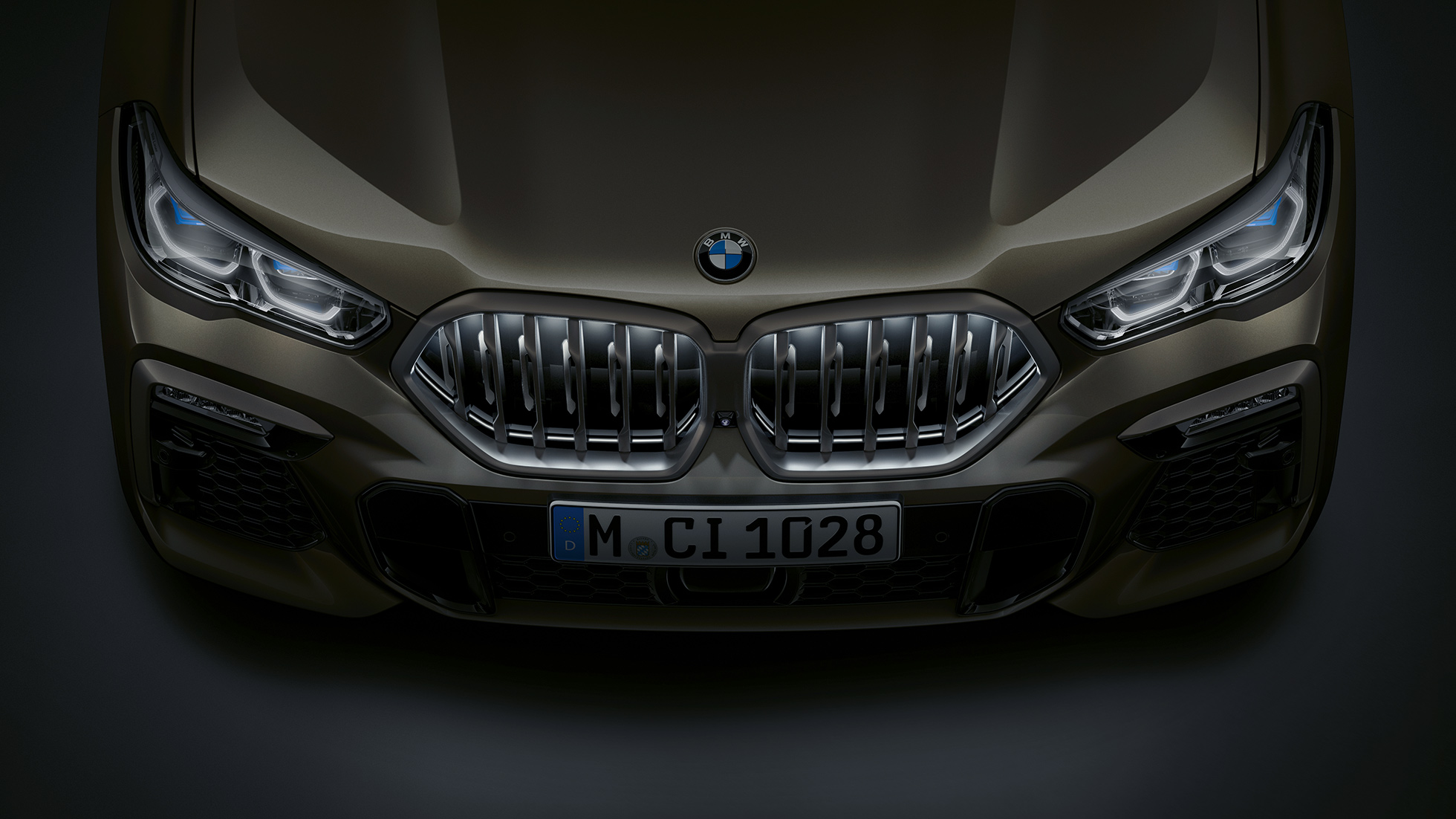 Close-up view of the BMW X6 front with BMW kidney grille 'Iconic Glow' from a bird's eye view.