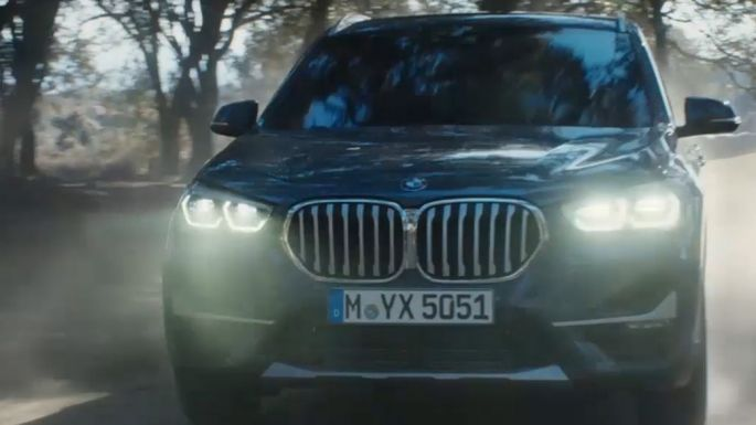 BMW X1, three-quarter front view driving in front nature scenery.